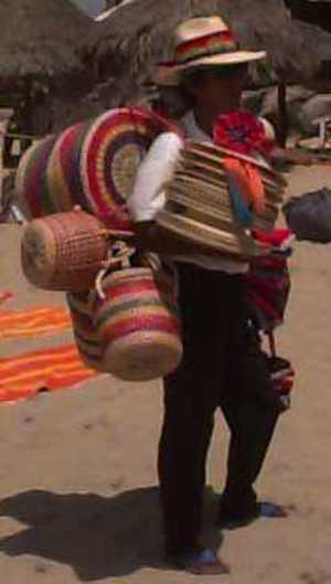 A picture of a man carrying hats, baskets, almost anything that can be made out of straw.